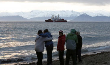 Local children stand on the shore as the Coast Guard ship Des Groseilliers sits in the waters near the Arctic community of Pond Inlet, Nunavut. (Photo: Chris Wattie/REUTERS)
