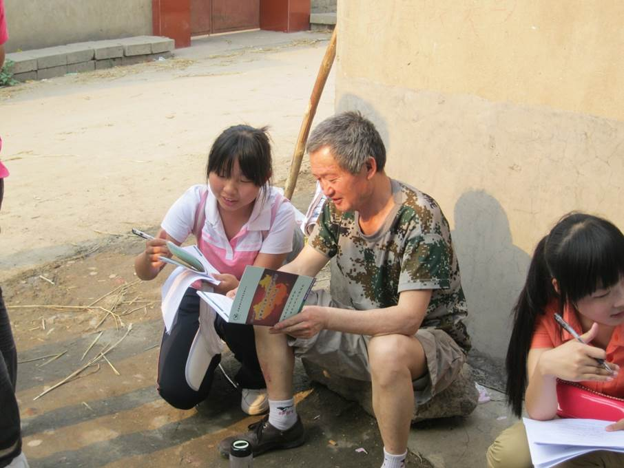 A volunteer discussing Green Anhui's new legal guide for pollution victims with a villager in Anhui Province, China.